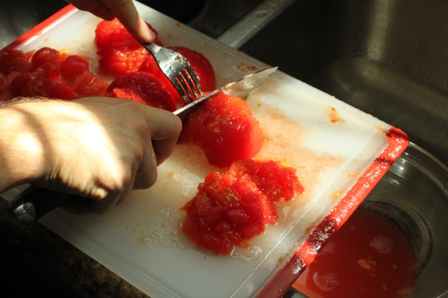 Chopping tomatoes.
